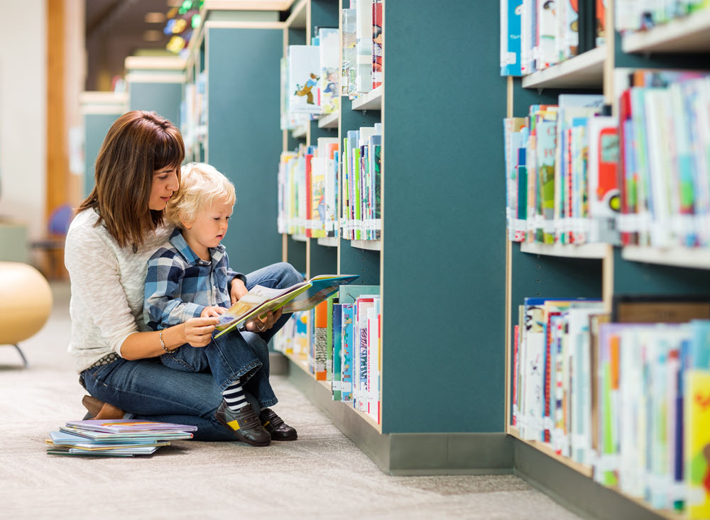 Image showing a woman reading to a child near library stacks