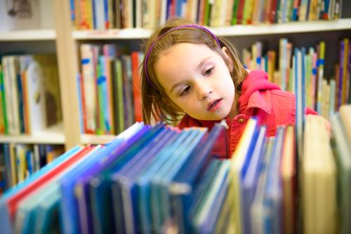 Image of girl browsing a shelf of books in a library